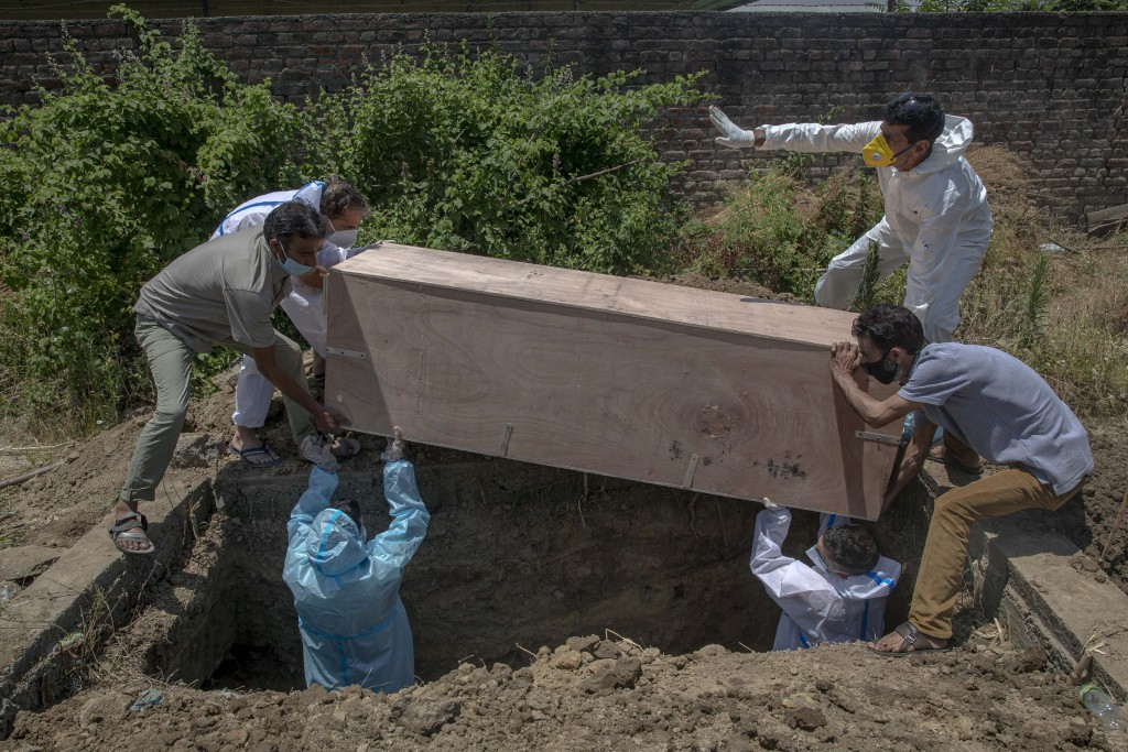 Relatives bury the body of a Kashmir man who died of COVID-19 at a cemetery in Srinagar, Indian controlled Kashmir, Friday, July 10, 2020. India has o...