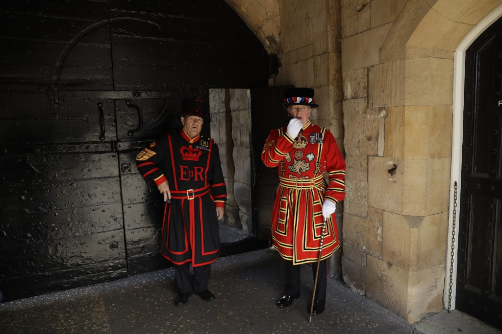Chief Yeoman Warder Peter McGowran, right, speaks on a radio flanked by Yeoman Gaoler Jim Duncan as they stand next to the gates at the main entrance ...