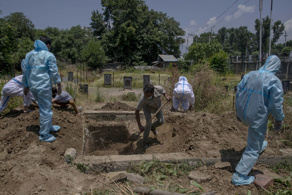 Relatives cover a grave of a relative who died of COVID-19 at a cemetery in Srinagar, Indian controlled Kashmir, Friday, July 10, 2020. India has over...