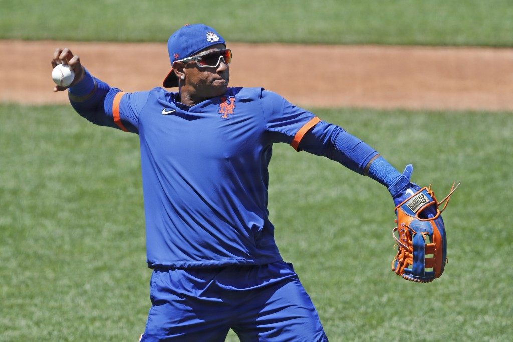 New York Mets left fielder Yoenis Cespedes stretches out to throw the ball as he waits for his turn in the batting cage during the afternoon session o...