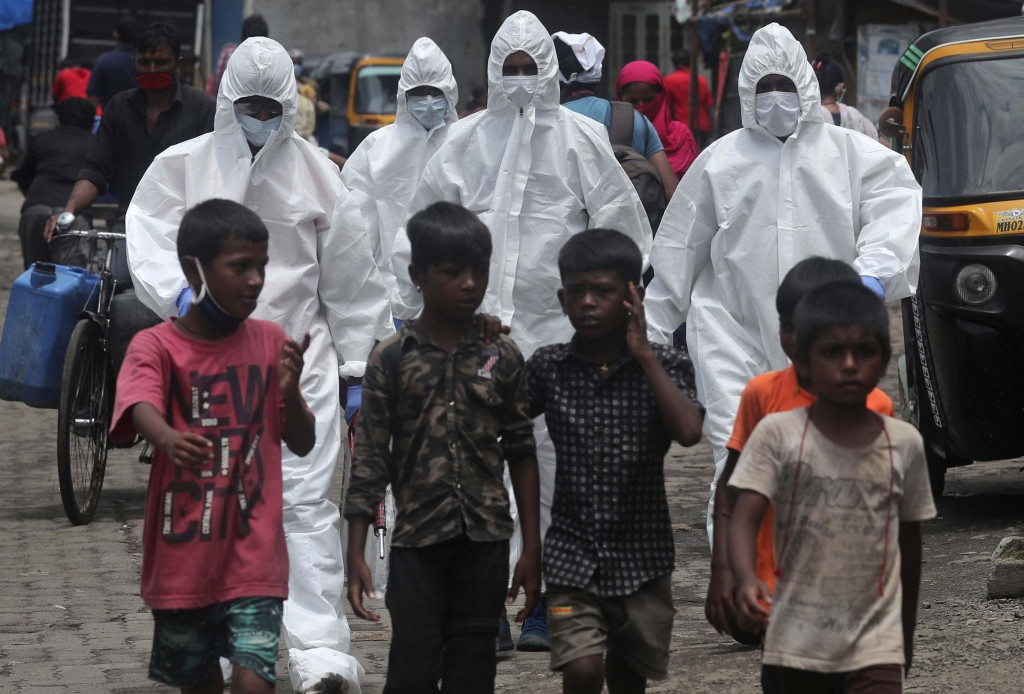 Health workers arrive to screen people for COVID-19 symptoms at a slum in Mumbai, India, Friday, July 10, 2020. India has overtaken Russia to become t...