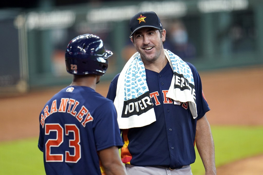 Houston Astros pitcher Justin Verlander, right, talks with Michael Brantley (23) after throwing during a simulated baseball game Thursday, July 9, 202...