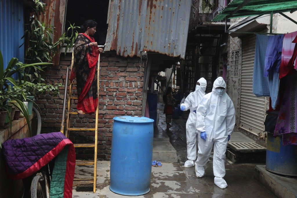 Health workers walk to screen people for COVID-19 symptoms at a slum, in Mumbai, India, Friday, July 10, 2020. India has overtaken Russia to become th...