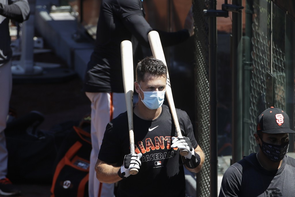 FILE - In this Sunday, July 5, 2020, file photo, San Francisco Giants' Buster Posey carries his bats during a baseball practice in San Francisco. Pose...