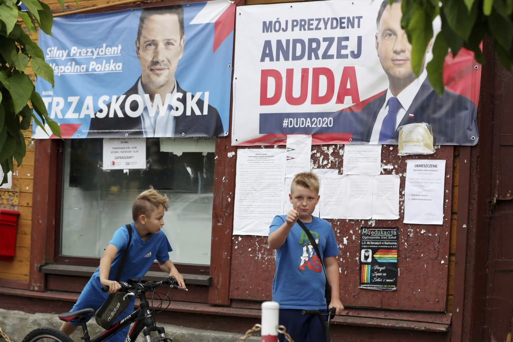 In this Thursday, July 9, 2020 photo election campaign posters of incumbent conservative president, Andrzej Duda, right, and his challenger, the liber...