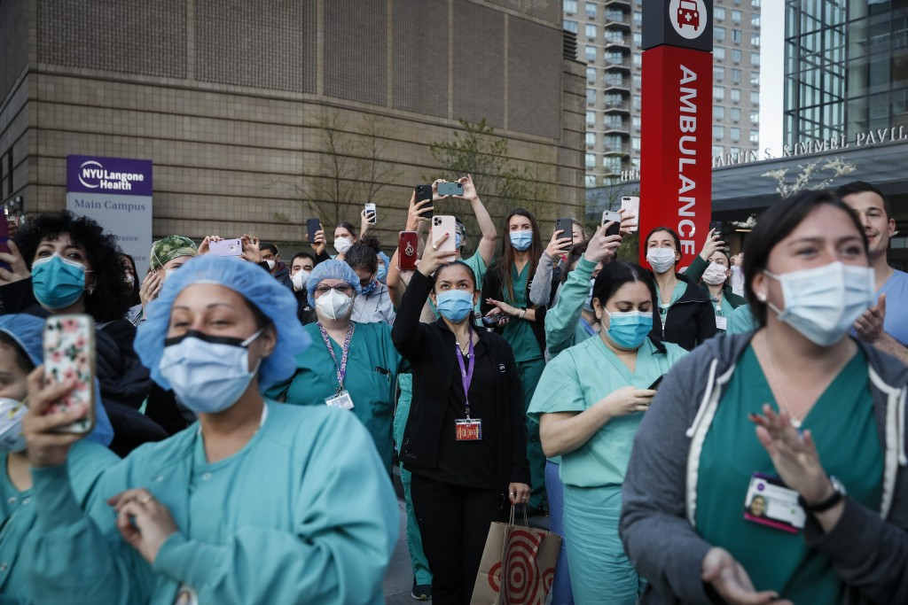 FILE - In this April 28, 2020, file photo Medical personnel attend a daily 7 p.m. applause in their honor, during the coronavirus pandemic outside NYU...