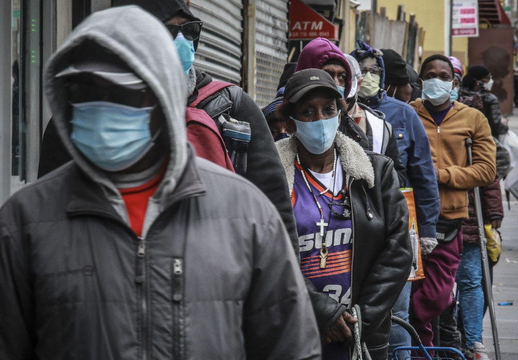 FILE - In this April 18, 2020, file photo, people wait for a distribution of masks and food from the Rev. Al Sharpton in the Harlem neighborhood of Ne...