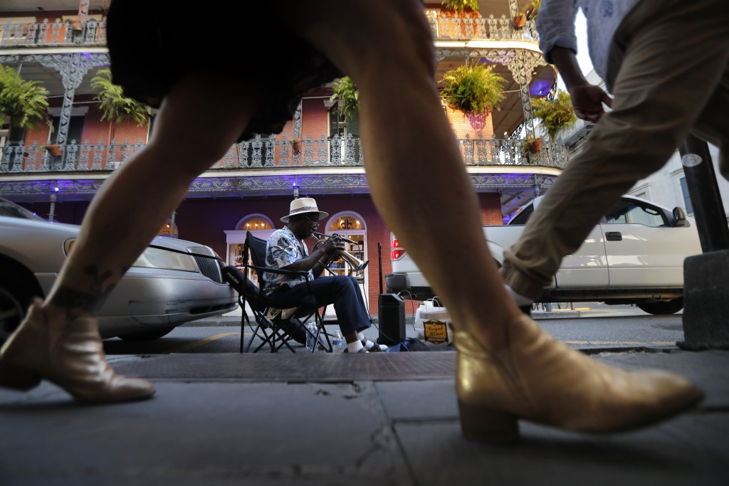 A musician plays his trumpet as pedestrians walk by on Royal Street in the French Quarter of New Orleans, Thursday, July 9, 2020. A sharp increase in ...