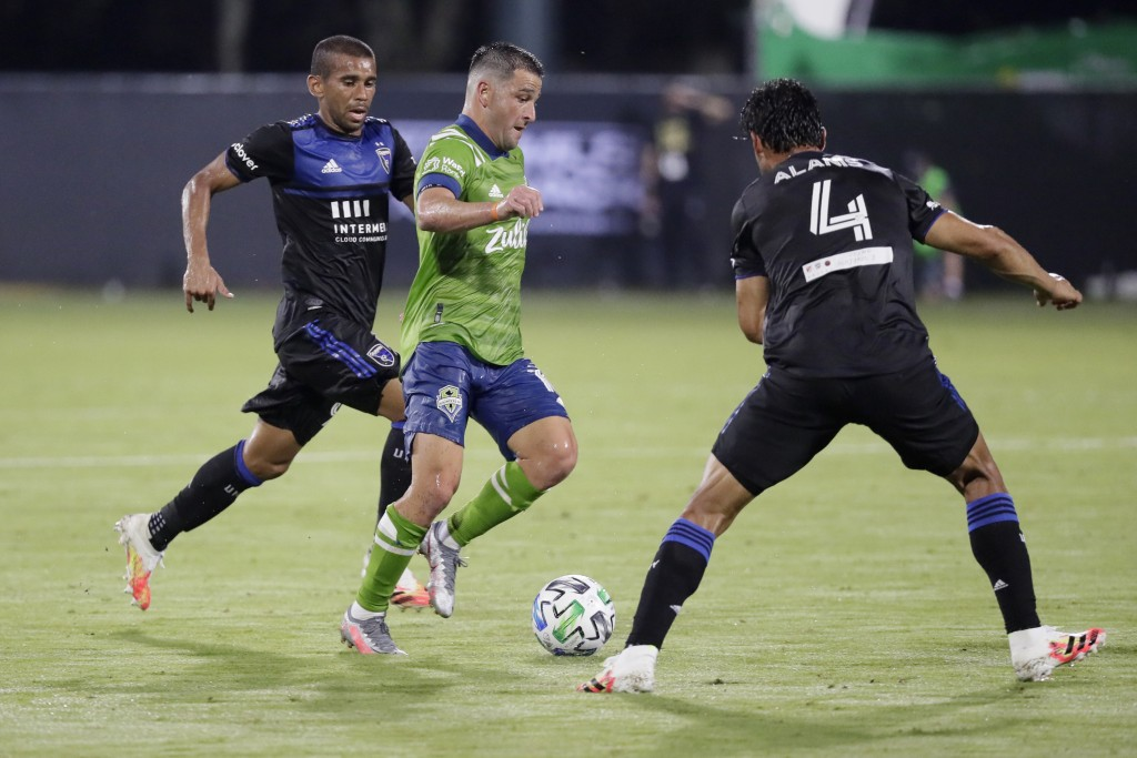 Seattle Sounders midfielder Nicolas Lodeiro, center, battles for the ball with San Jose Earthquakes midfielder Judson, left, and defender Oswaldo Alan...