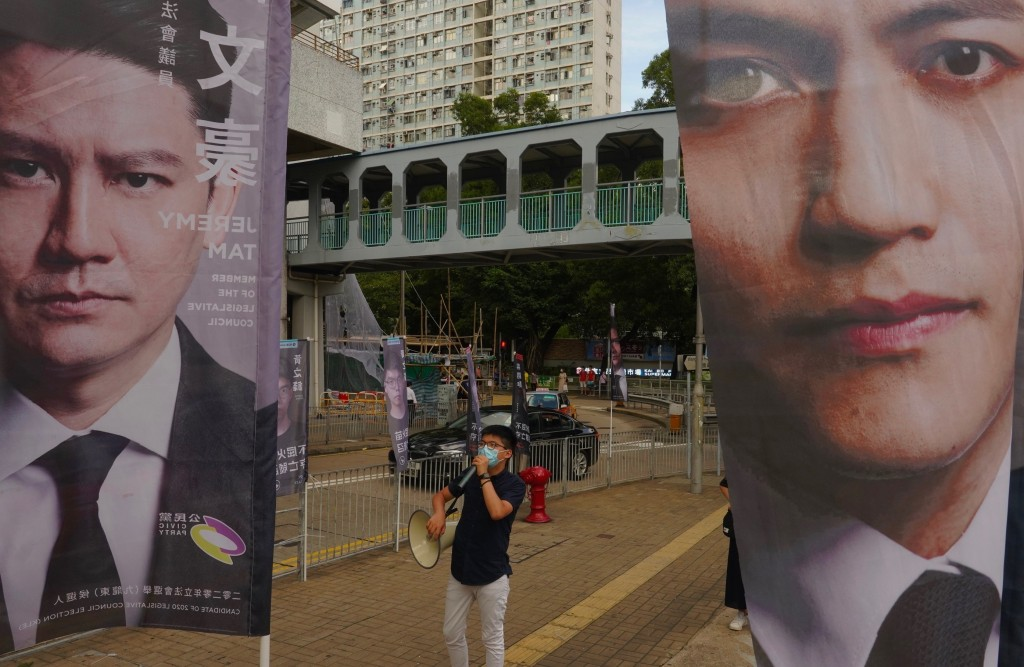 Activist Joshua Wong uses a loudspeaker to urge passers-by in between candidates banners outside a subway station to take part in voting in Hong Kong ...