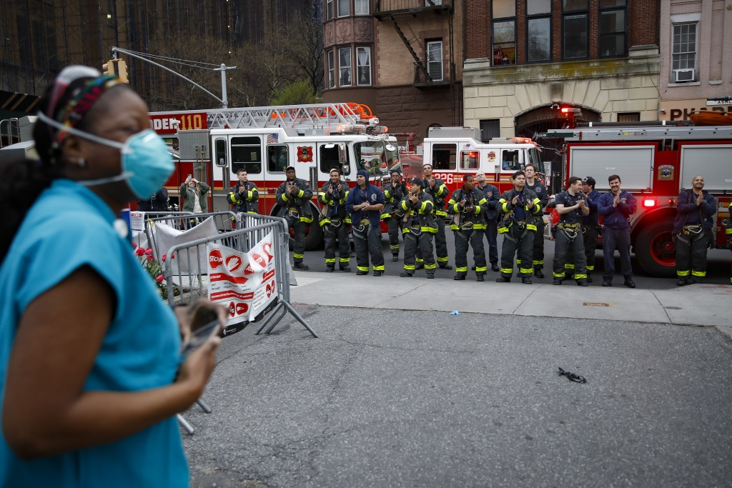 FILE - In this April 14, 2020, file photo FDNY firefighters gather to applaud medical workers as attending physician Mollie Williams, left, wears pers...