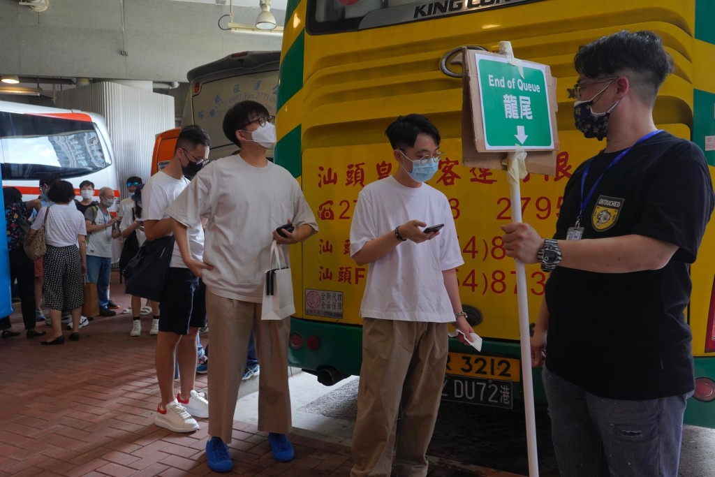 """People wearing face masks queue up to vote in Hong Kong Saturday, July 11, 2020, in an unofficial """"primary"""" for pro-democracy candidates ahead of legi..."""