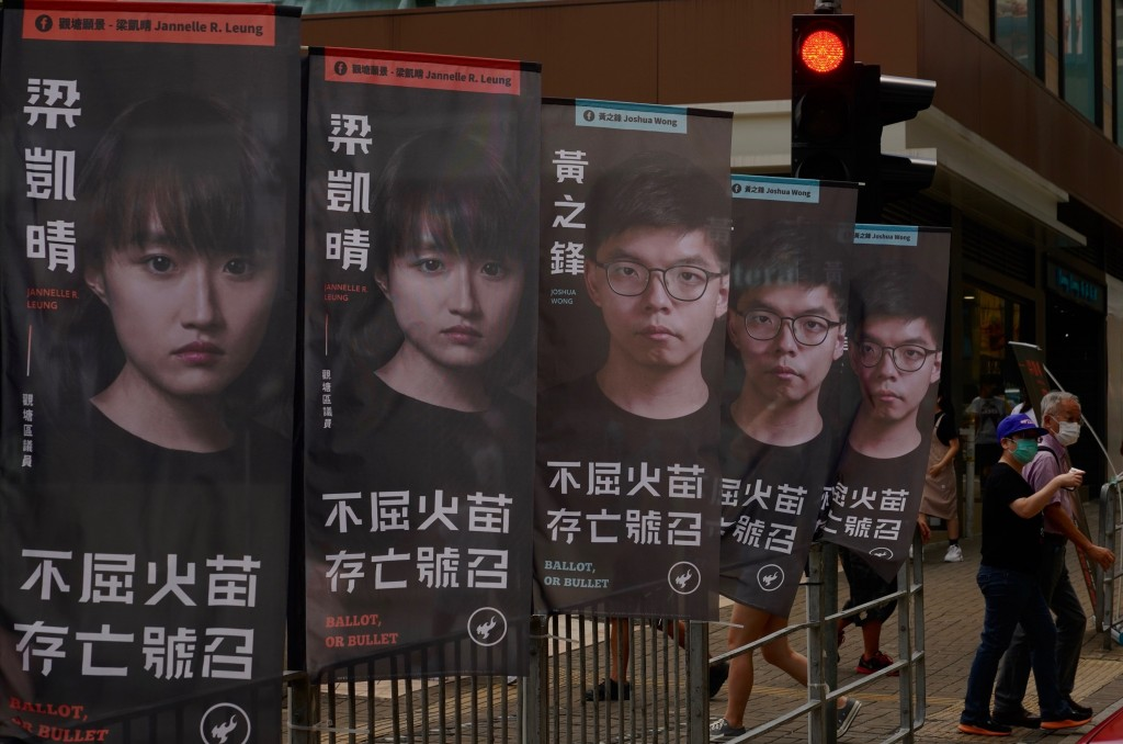 Banners of a pro-democracy candidate Joshua Wong, wearing glasses, are displayed outside a subway station in Hong Kong Saturday, July 11, 2020, in an ...