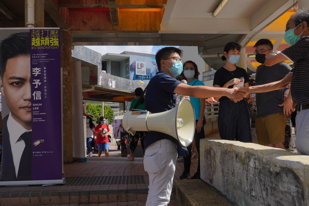 Activist Joshua Wong shakes hands with a supporter as he urges passers-by outside a subway station to take part in voting in Hong Kong Saturday, July ...