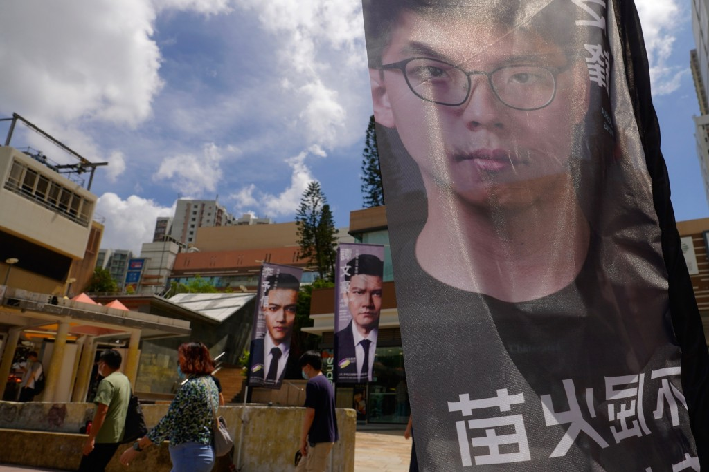 A banner of pro-democracy candidate Joshua Wong, right, is displayed outside a subway station for voting in Hong Kong Saturday, July 11, 2020, in an u...