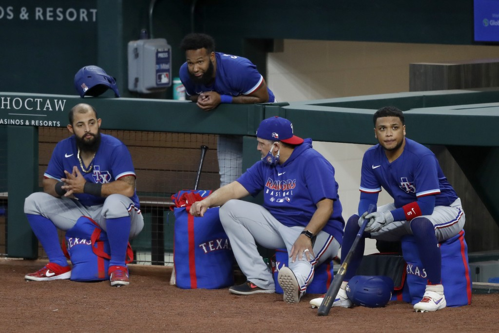 Texas Rangers' Rougned Odor, left, Danny Santana, top, catching coach Hector Ortiz and Willie Calhoun, right, participate in an intrasquad game during...