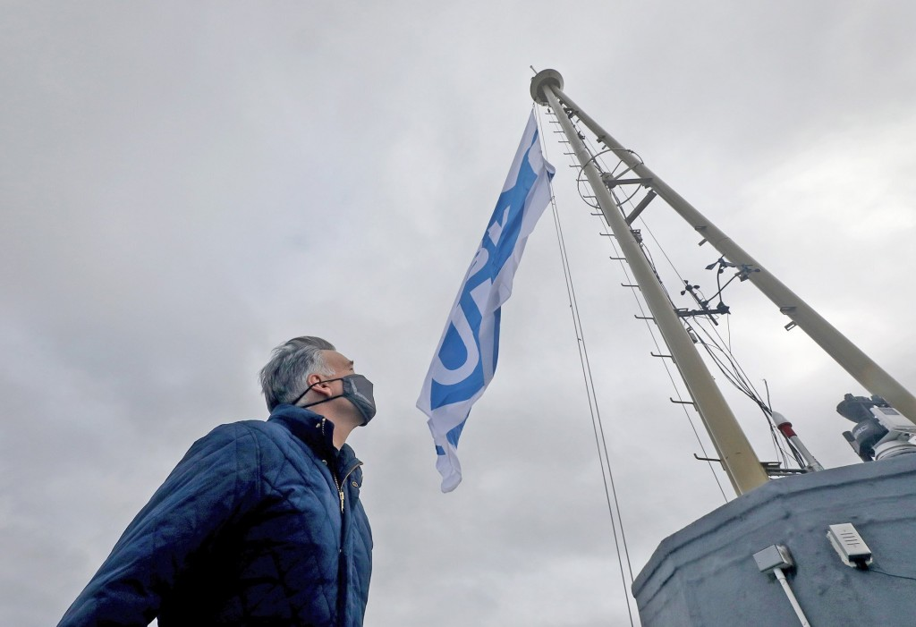 "King County Executive Dow Constantine watches a flag that reads ""Mask Up"" on top of the Space Needle in Seattle, Friday, July 10, 2020. Statewide, eve..."