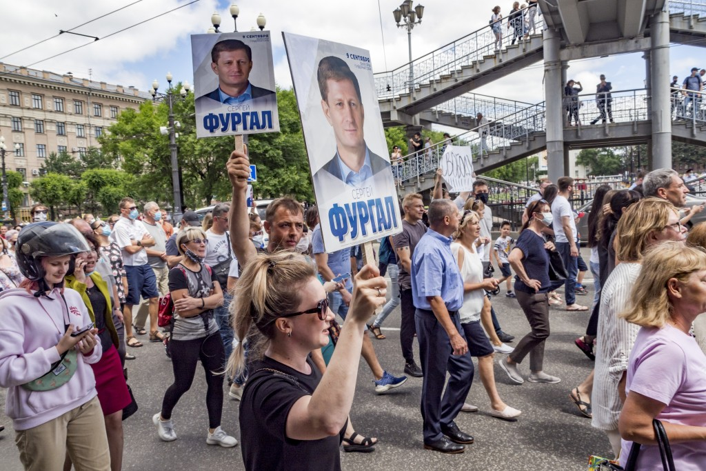 People hold up posters with portraits of Sergei Furgal during an unsanctioned protest in Khabarovsk, 6100 kilometers (3800 miles) east of Moscow, Russ...