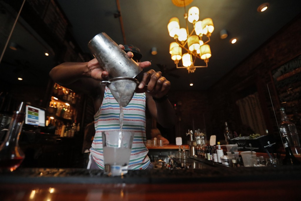 Bartender Brendan Donald makes cocktails inside Bar Tonique in New Orleans, Thursday, July 9, 2020. A sharp increase in COVID-19 cases and hospitaliza...