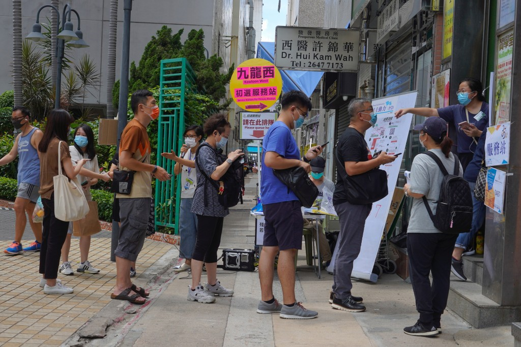"""People queue up to vote in Hong Kong Saturday, July 11, 2020, in an unofficial """"primary"""" for pro-democracy candidates ahead of legislative elections i..."""