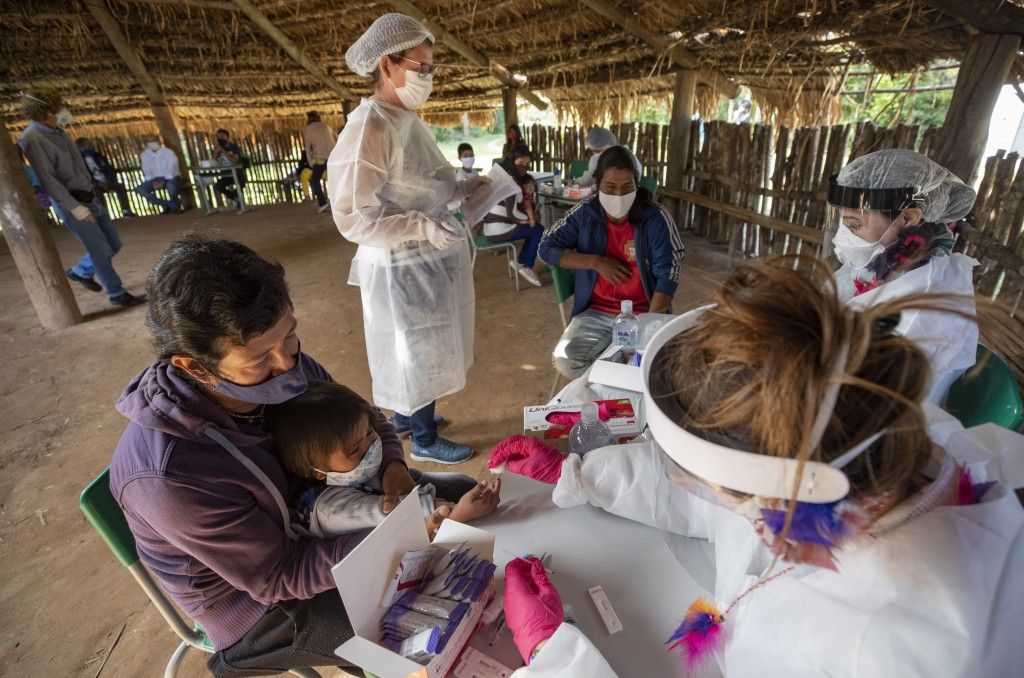 Health workers from the Butantan Institute test Guarani Mimbya Indigenous for COVID-19 in their community in Cananeia, Brazil, Friday, July 10, 2020. ...