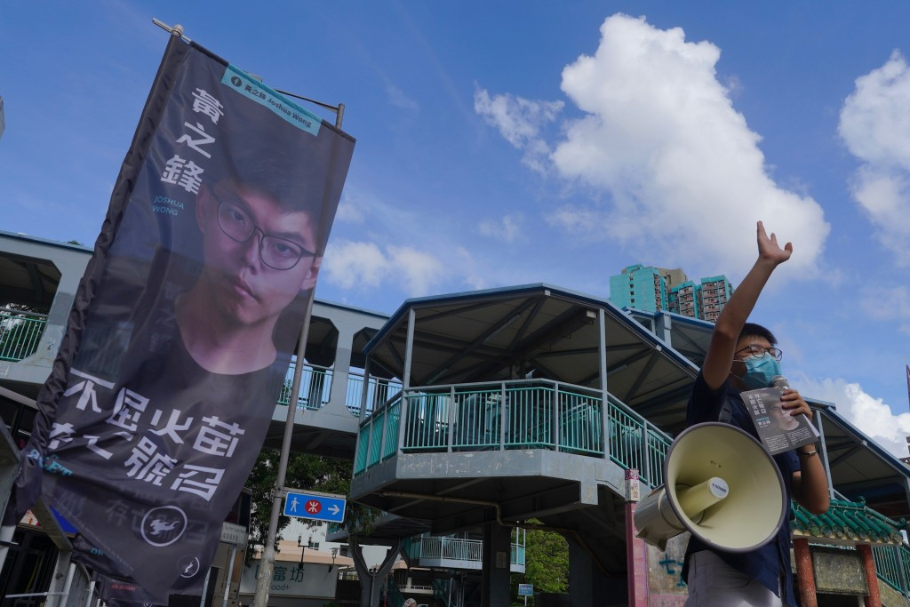Activist Joshua Wong uses a loudspeaker to urge passers-by outside a subway station to take part in voting in Hong Kong Saturday, July 11, 2020, in an...