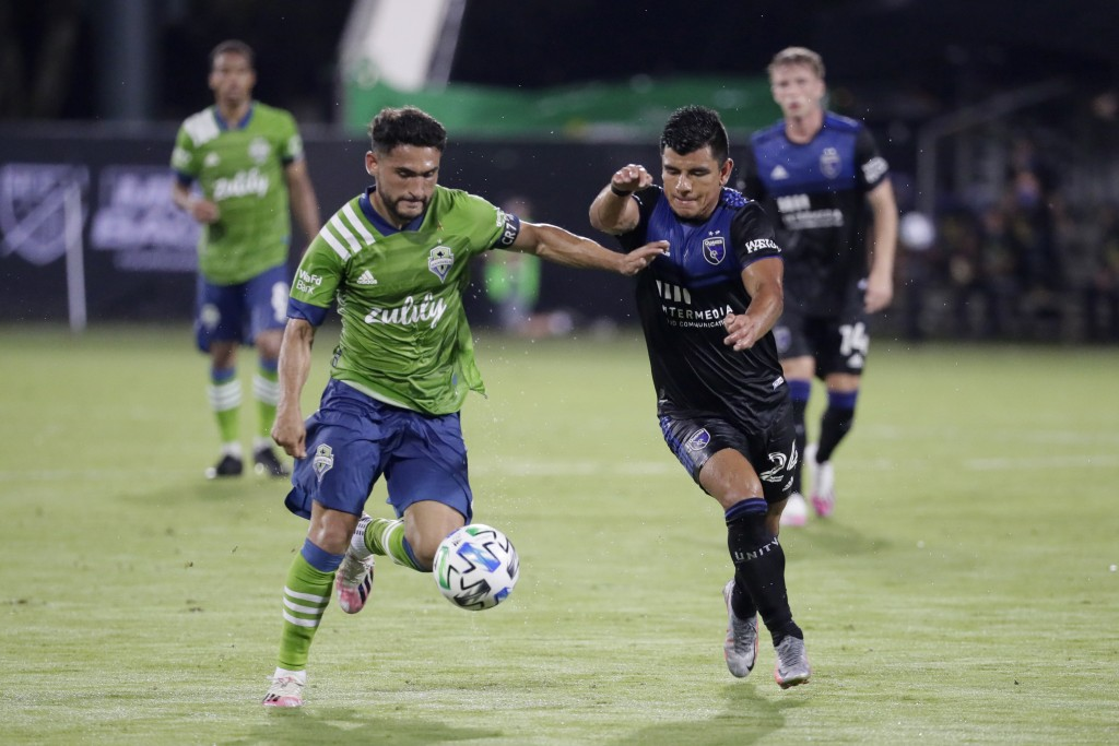 Seattle Sounders midfielder Cristian Roldan, left, moves the ball against San Jose Earthquakes defender Nick Lima during the first half of an MLS socc...