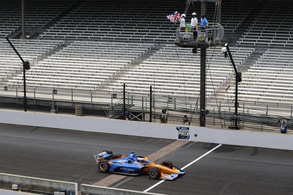 FILE - In this Saturday, July 4, 2020, file photo, race driver Scott Dixon, of New Zealand, takes the checkered flag as he crosses the start/finish li...