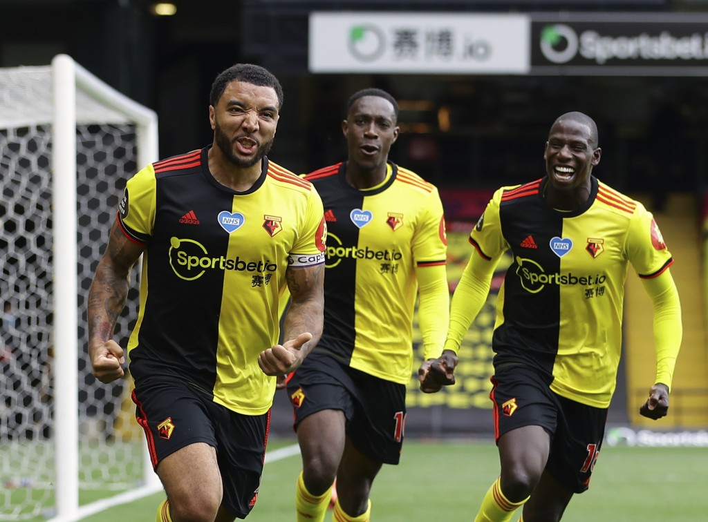 Watford's Troy Deeney, left, celebrates with teammates after scores his side's second goal from the penalty spot during the English Premier League soc...
