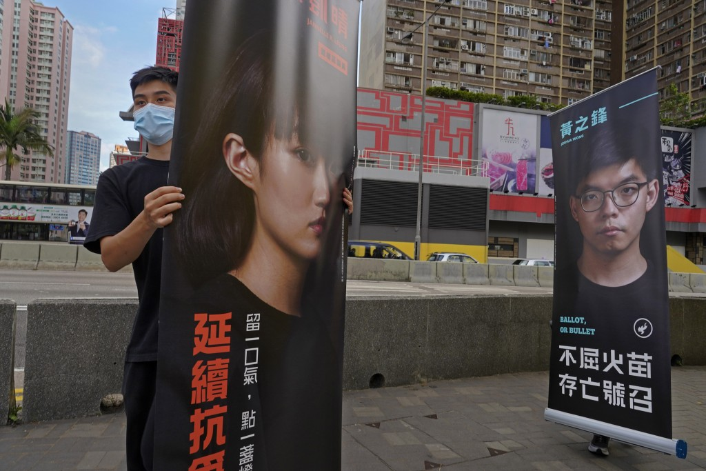 Banners of pro-democracy candidates Jannelle Leung, left, and Joshua Wong are carried by supporters outside a subway station in Hong Kong Saturday, Ju...