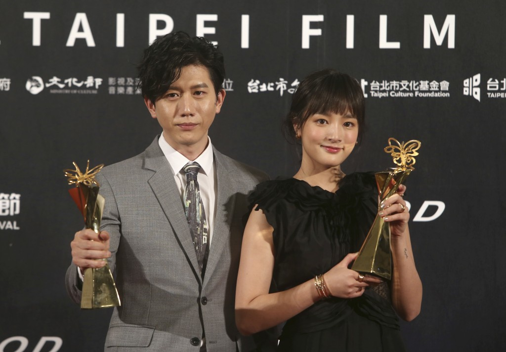 Taiwanese actress Gingle Wang, right, and Taiwanese actor Mo Tzu-yi hold their awards for Best Actress and Best Actor at the 2020 Taipei Film Festival...