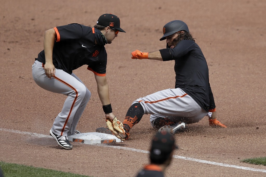 San Francisco Giants' Brandon Crawford, right, slides into the tag of third baseman Will Wilson during a baseball practice on Friday, July 10, 2020, i...