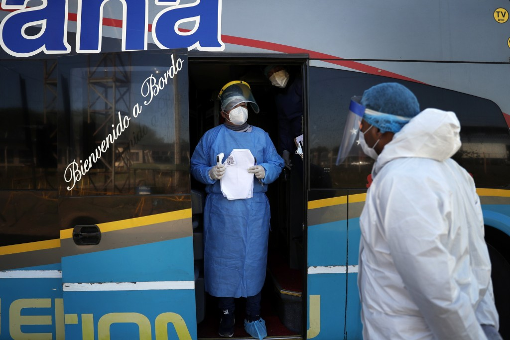 A worker from the Paraguayan Public Health Ministry stands after his team conducted passenger control on a bus that was specially organized to bring p...