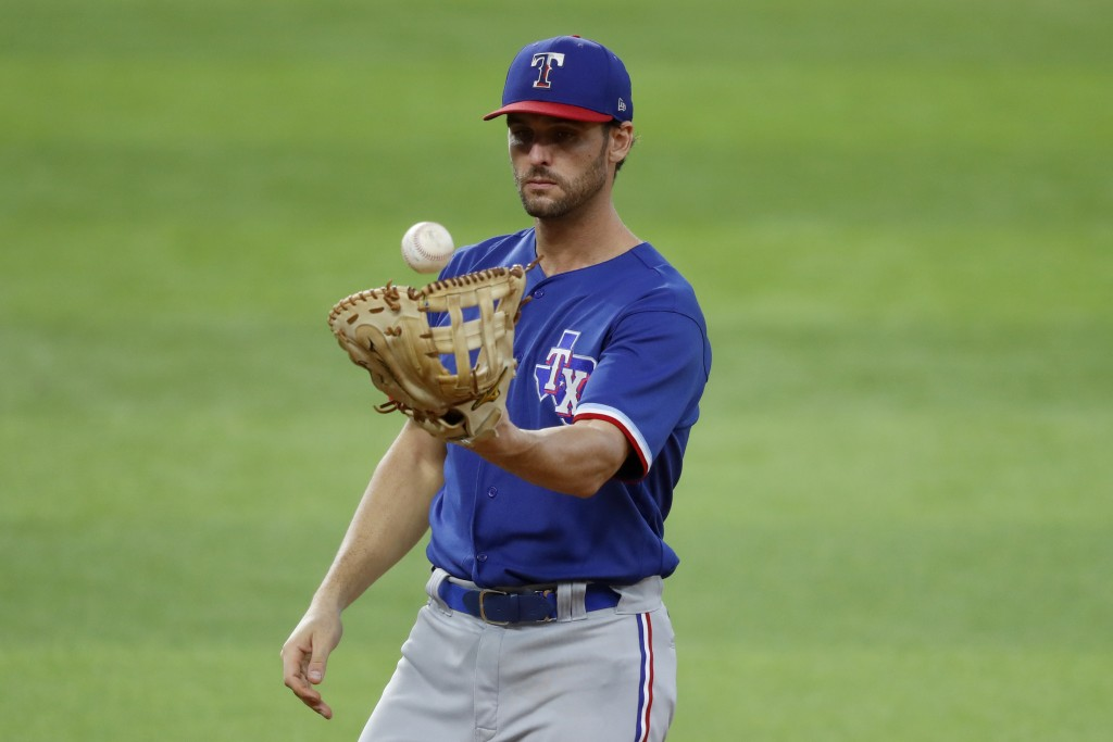 Texas Rangers infielder Greg Bird tosses a ball in his glove in an intrasquad game during baseball practice at Globe Life Field in Arlington, Texas, F...