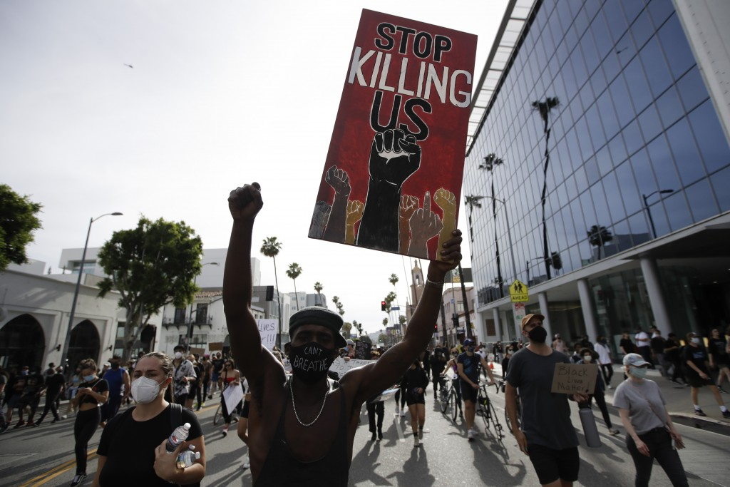 FILE - In this June 1, 2020, file photo, a protester carries a sign in the Hollywood area of Los Angeles during demonstrations over the death of Georg...