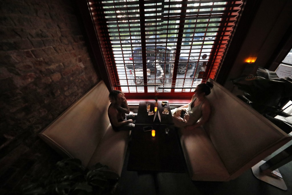 Patrons sit in a booth inside Bar Tonique in New Orleans, Thursday, July 9, 2020. A sharp increase in COVID-19 cases and hospitalizations is forcing b...