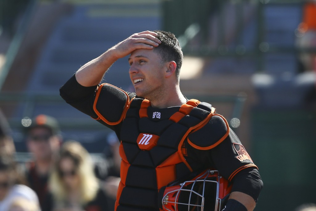 FILE - In this Monday, Feb. 24, 2020, file photo, San Francisco Giants catcher Buster Posey wipes sweat from his forehead during the first inning of a...