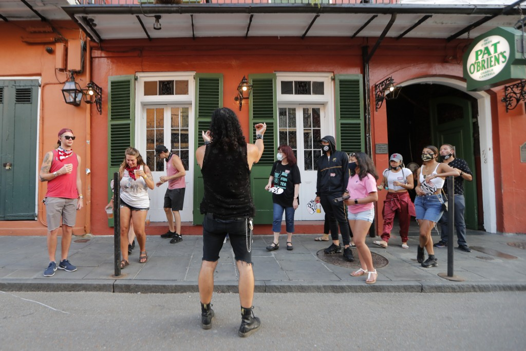 A walking tour guide assembles in front of Pat O'Brien's Bar in the French Quarter of New Orleans, Thursday, July 9, 2020. A sharp increase in COVID-1...