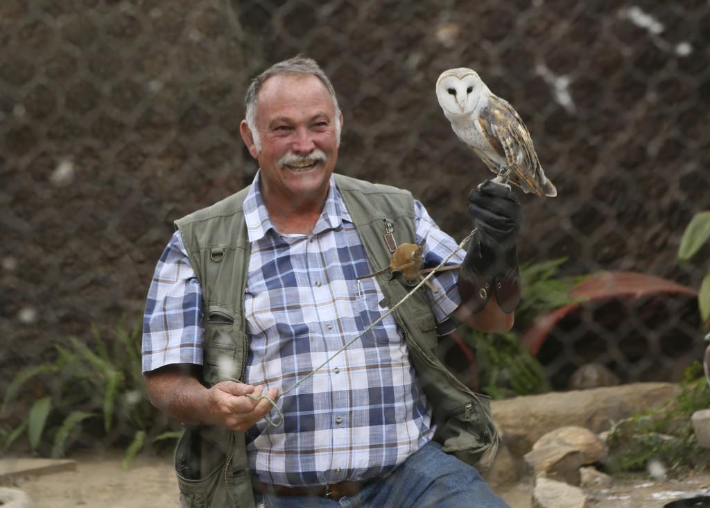 Gary Strafford, a Zimbabwean falconer, holds an owl inside one of the cages at his bird sanctuary, Kuimba Shiri, near Harare, Zimbabwe, Wednesday, Jun...