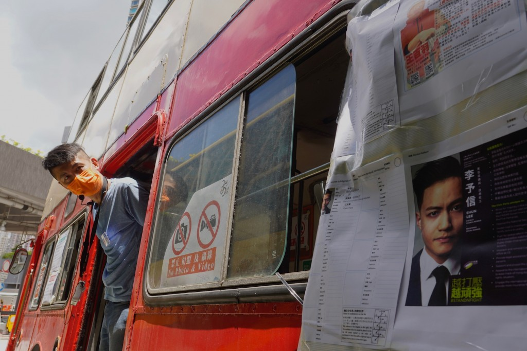 A volunteer wearing a face mask looks out from a vintage double-decker bus used as a polling center in voting in Hong Kong Saturday, July 11, 2020, in...