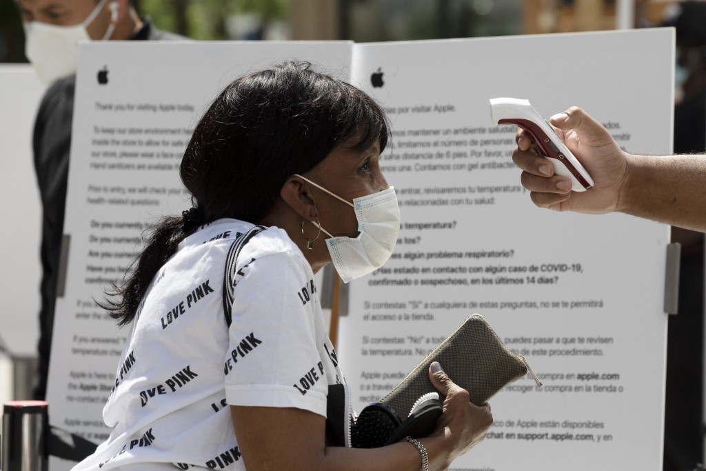 A customer has her temperature checked before entering the Apple Store, Saturday, July 11, 2020, in Boston. (AP Photo/Michael Dwyer)