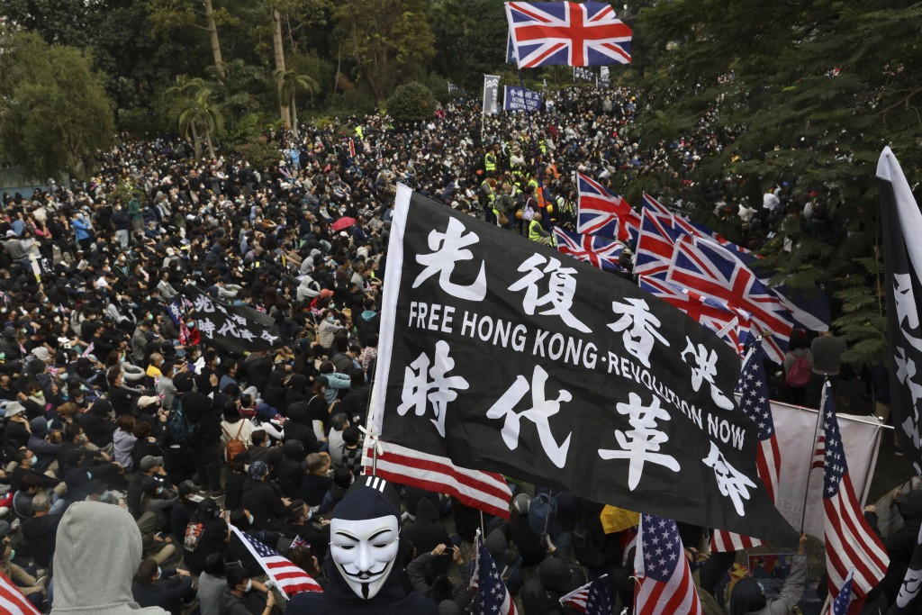 FILE - In this Sunday, Jan. 19, 2020 file photo, participants wave British and U.S. flags during a rally demanding electoral democracy and call for bo...