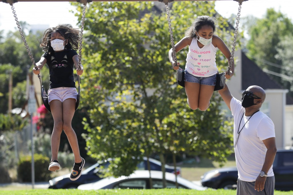 Afework Meshesha, right, pushes his daughter Yohanna while she rides a swing at a playground, Saturday, July 11, 2020, in Los Angeles. The number of d...