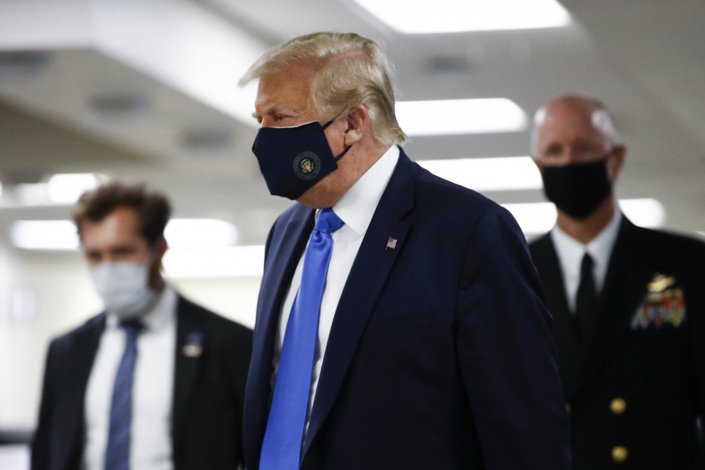 President Donald Trump wears a mask as he walks down the hallway during his visit to Walter Reed National Military Medical Center in Bethesda, Md., Sa...