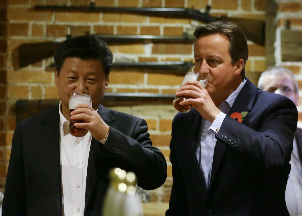 FILE - In this Thursday, Oct. 22, 2015 file photo, Britain's Prime Minister David Cameron, right, drinks beer with Chinese President Xi Jinping, at a ...