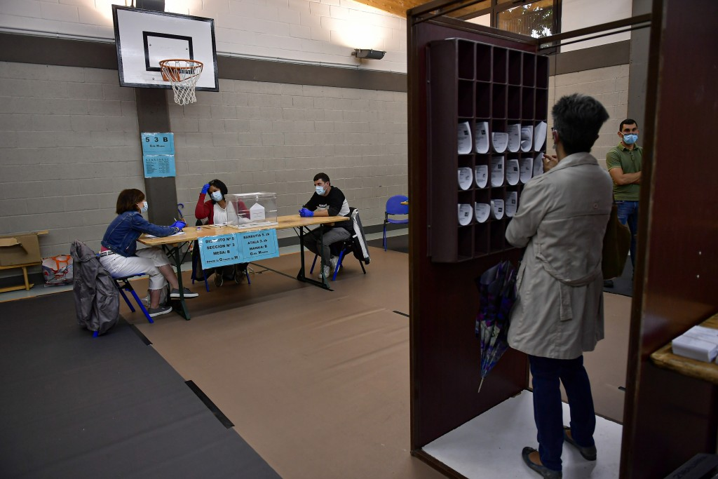 A woman prepares her vote while staff members of a polling station wear face masks to help curb the spread of the coronavirus during the Basque region...