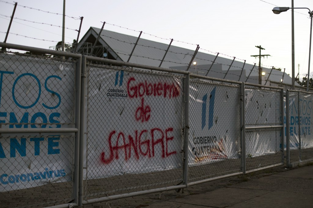 """Graffiti that reads in Spanish: """"Blood Government,"""" is painted on a fence of a temporary hospital for coronavirus patients in Guatemala City, Saturday..."""
