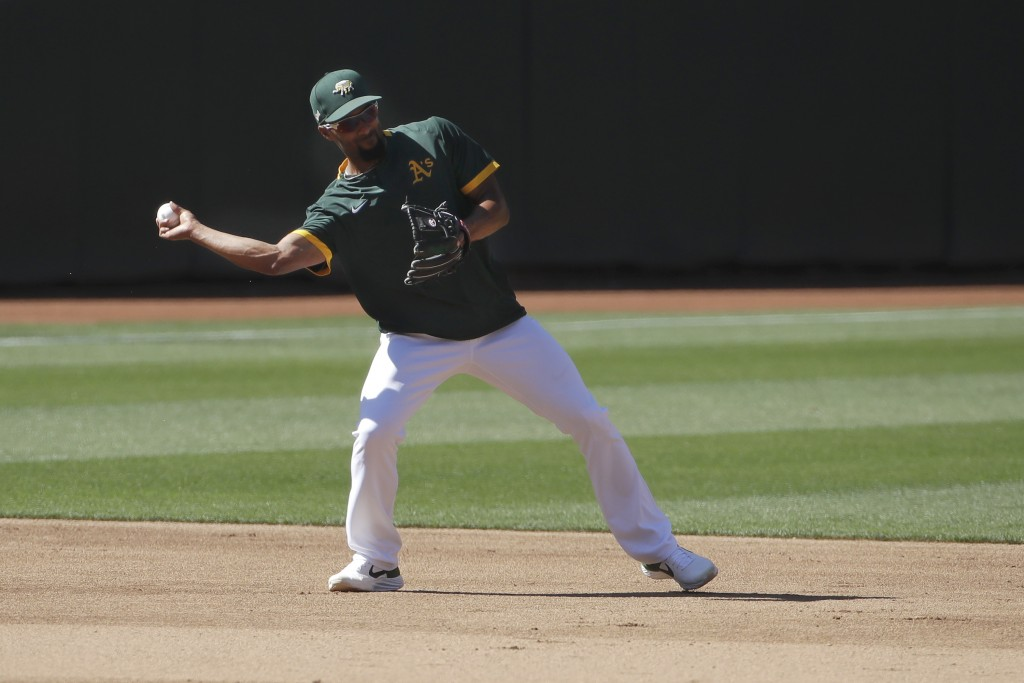 Oakland Athletics shortstop Marcus Semien throws during a baseball practice in Oakland, Calif., Saturday, July 11, 2020. (AP Photo/Jeff Chiu)