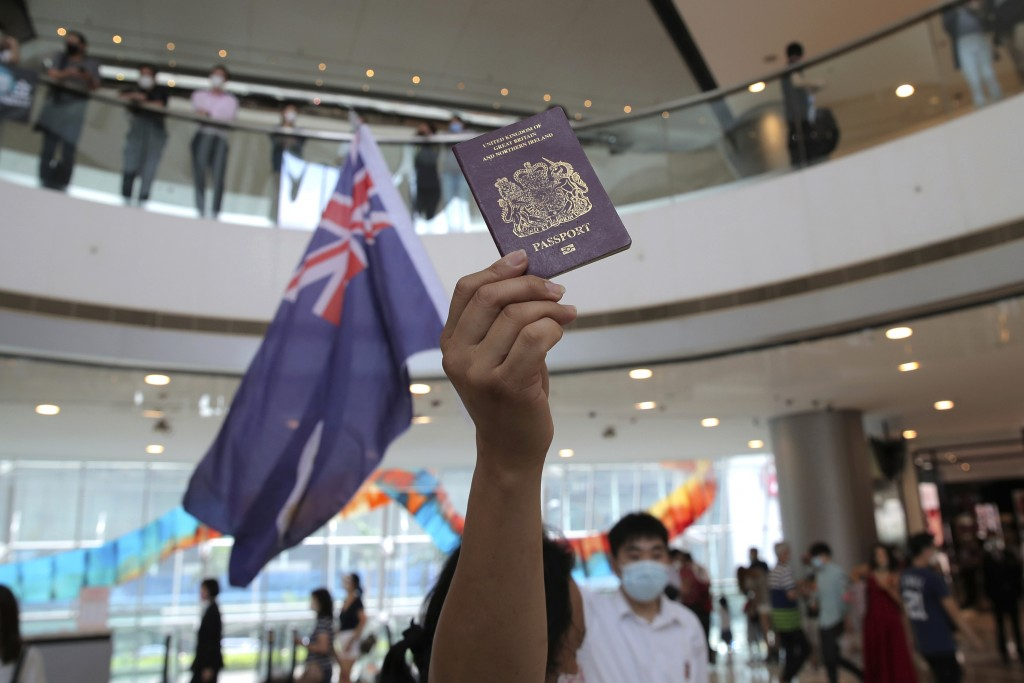 FILE - In this Friday, May 29, 2020 file photo, protesters hold a British National (Overseas) passport and Hong Kong colonial flag in a shopping mall ...