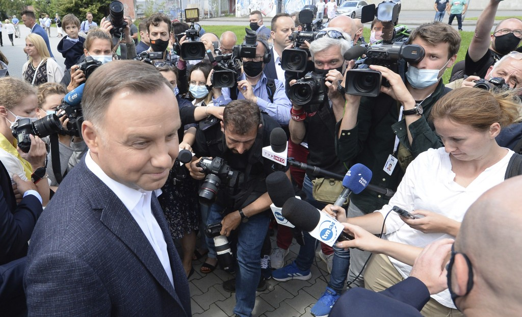 Candidate in Poland's tight presidential election runoff, incumbent President Andrzej Duda talks to reporters after having cast his ballot at a pollin...